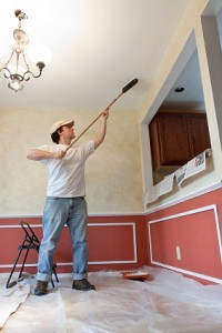 Man painting the ceiling of room with a roller